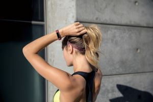 Alta HR lifestyle shot featuring a blonde woman tightening her hair tie wearing the fuchsia classic band.